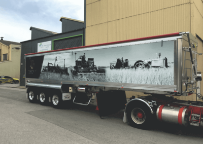 A semi's very long trailer features a dramatic large format printed sign on the trailers side