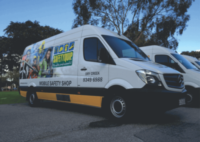 A safety equipment delivery van featuring large format printed signs and vinyl cut words applied to the side the van