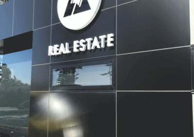 A 3 D lettering sign mounted with a back lit sign outside a real estate office
