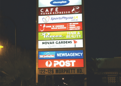 An outside pylon sign with back lit panels for shopping centre
