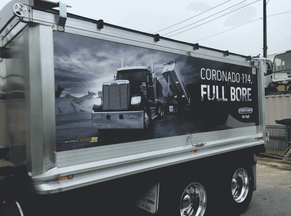 A tandem tipper's trailer has a large format black and white (photo) digital sign applied to both sides