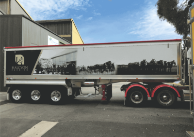 A long trailer on a semi features a generational large format printed sign