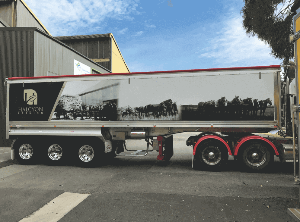 A semi's trailer has a large format black and white (photo) digital sign applied to both sides