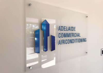 A custom made glass rectangular sign with vinyl cut lettering and 3D lettering hung in an office reception area