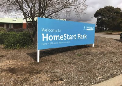 A large traditional outdoor sign featuring vinyl cut lettering erected in a park in Adelaide promoting Homestart park