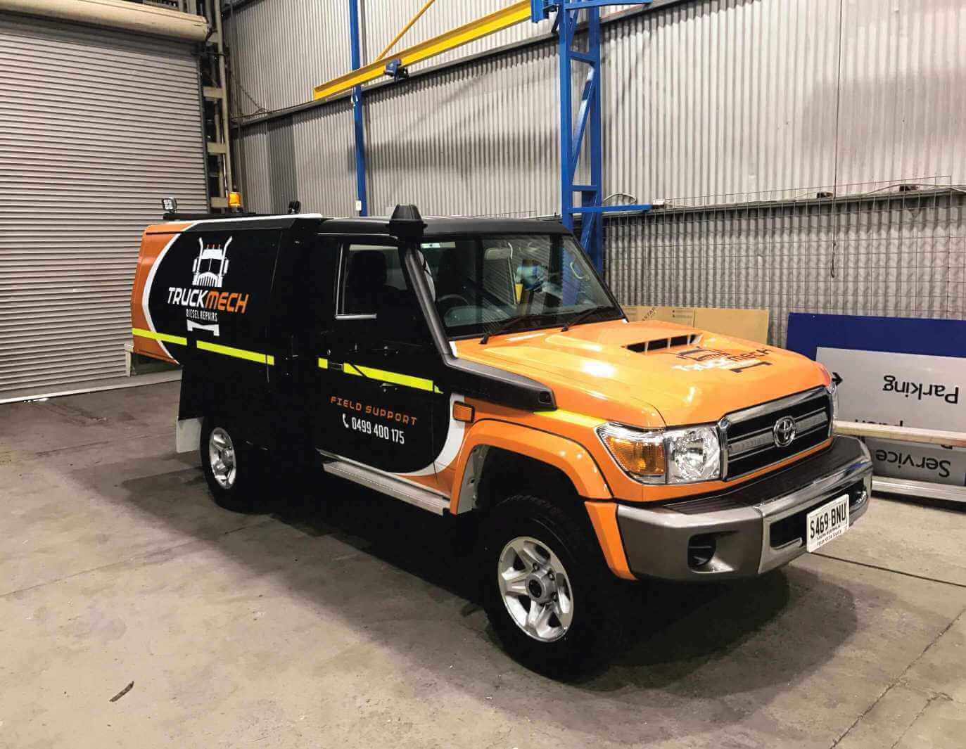 Vehicle decals and lettering - A field service support vehicle which has been spray painted in three different colours and has had vehicle decals and lettering applied